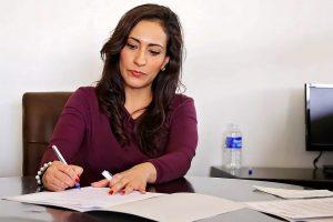 Mujer firmando una carta de renuncia de trabajo